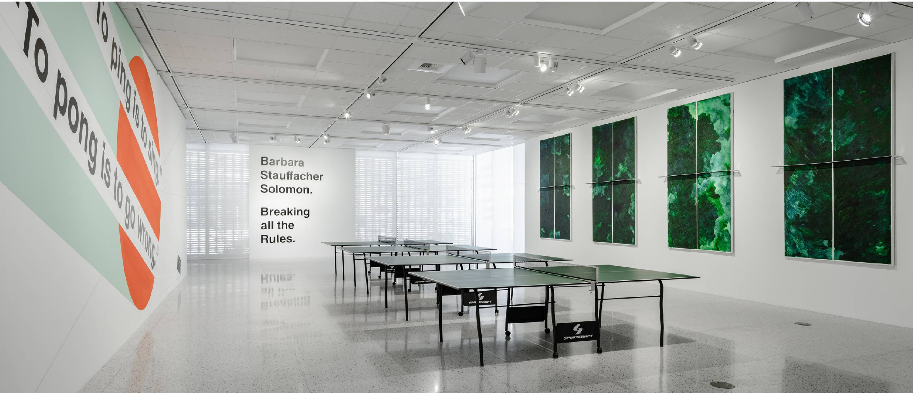 Main gallery with ping pong tables and artworks on the walls