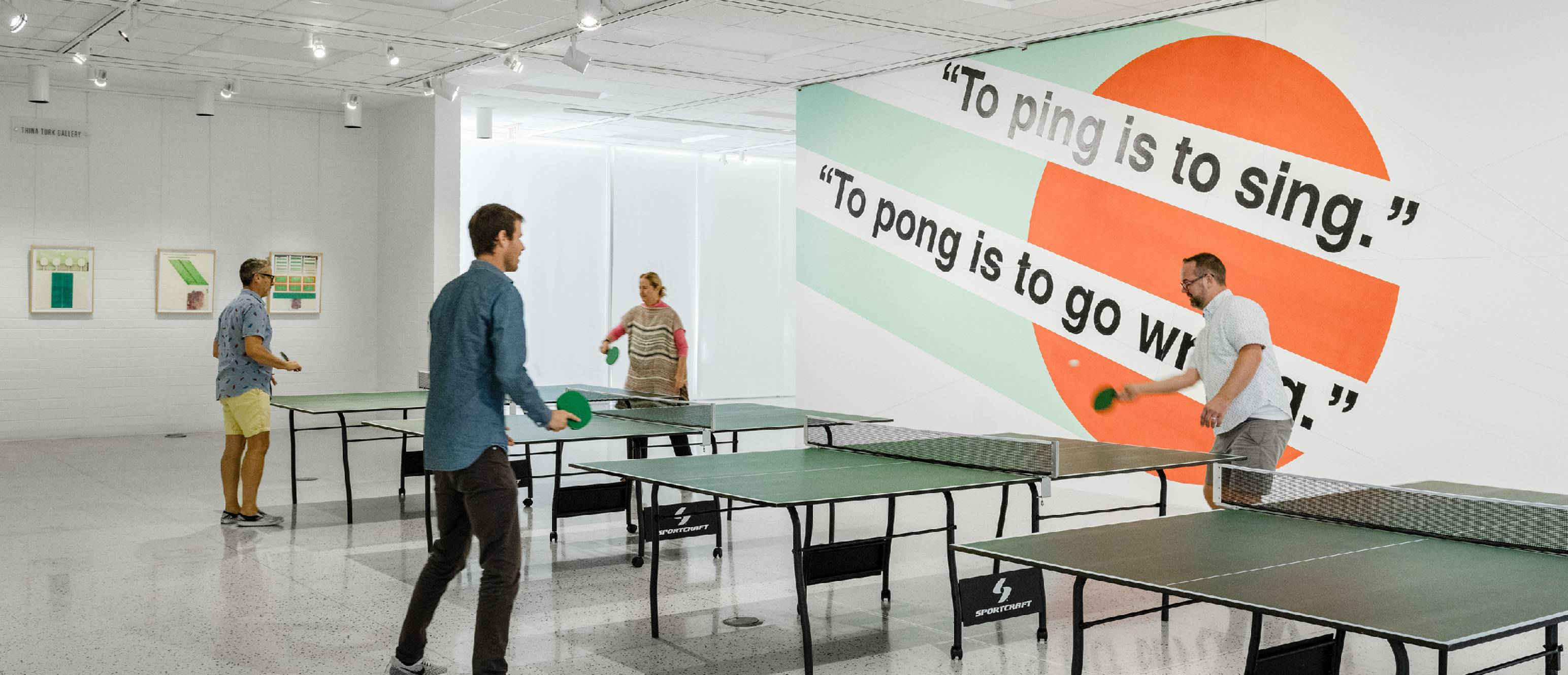 People playing ping pong in the gallery