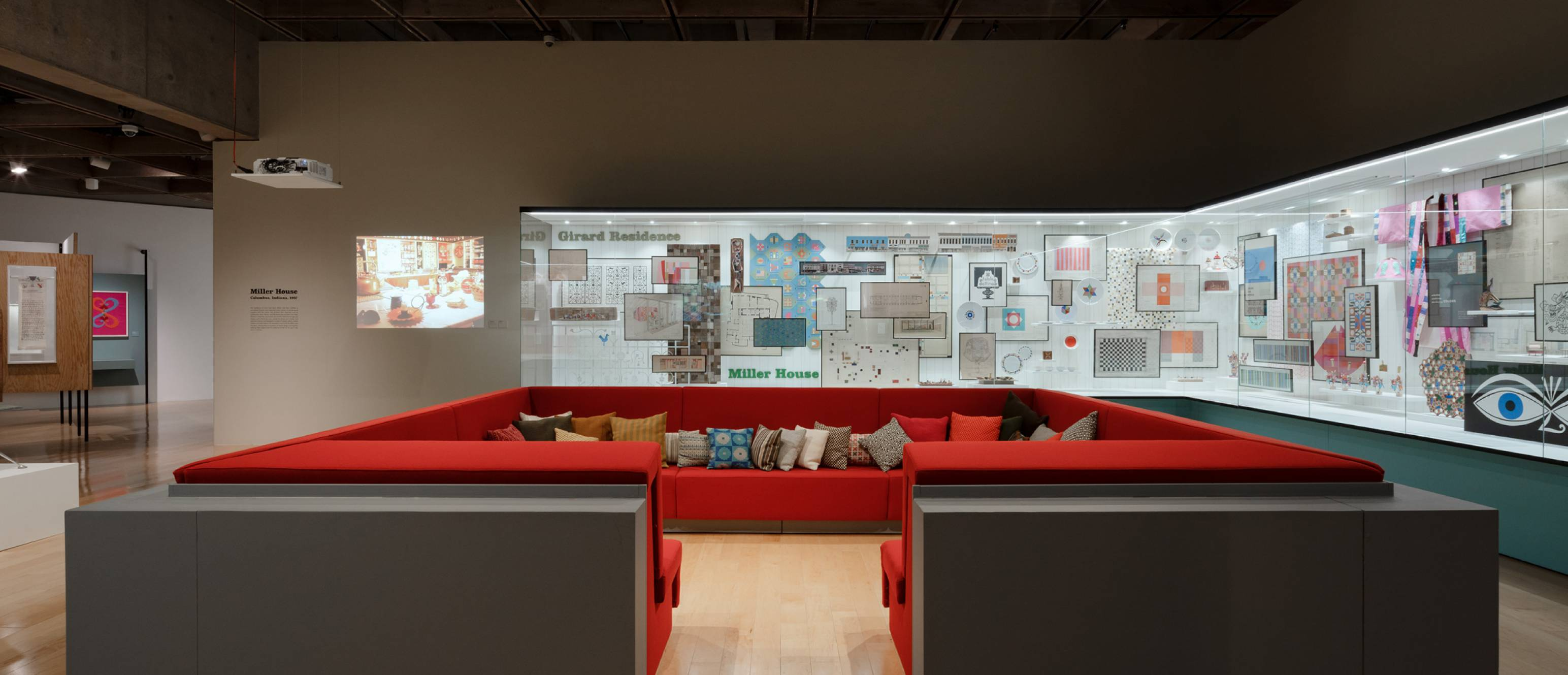 Alexander Girard exhibition, Conversation pit made of red pillows with glass gallery in the back